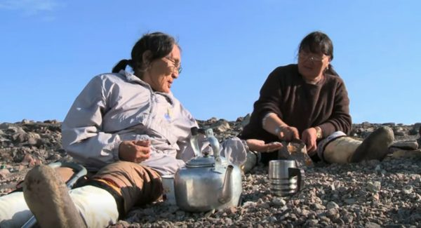 two inuit people drinking tea