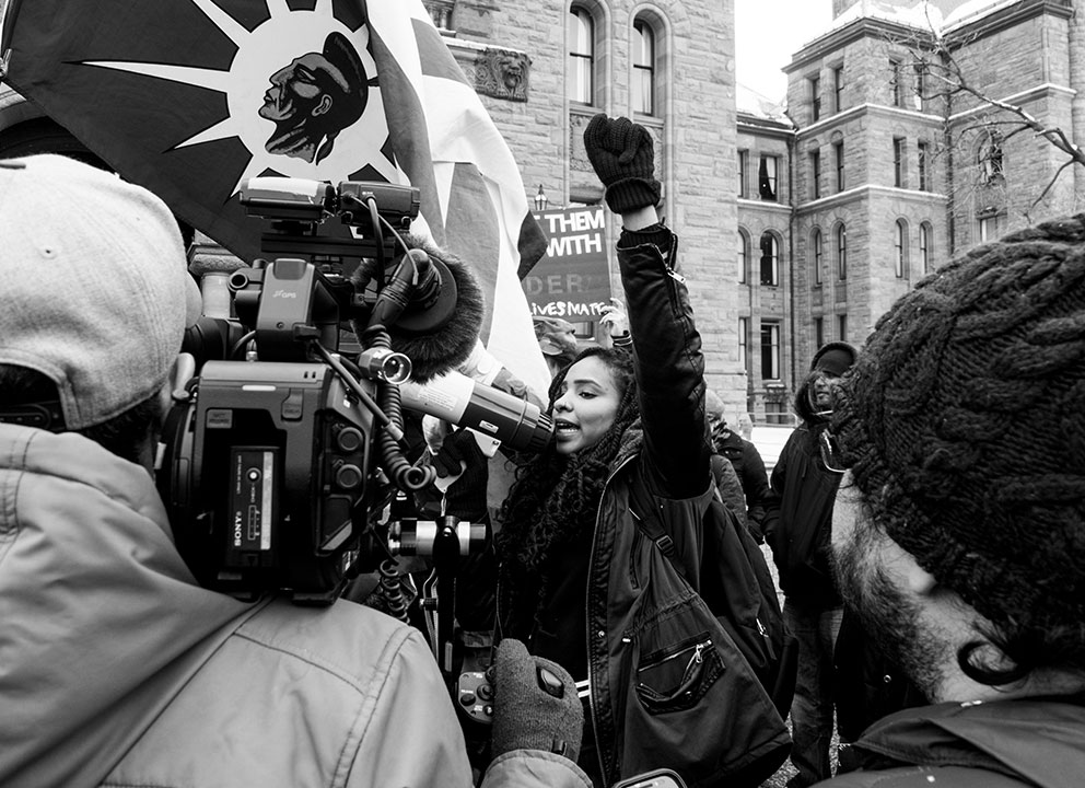 A woman with a megaphone raises her fist in the air at a Black Lives Matter protest.