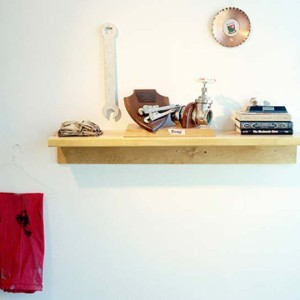 shelf holding books, trophy and a wrench on a white background with a hanger and a red towel below