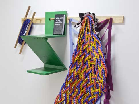 close up of a clothing hook with a green wooden geometric object, a multicoloured woven object and purple ribbon. All hanging off pegs.