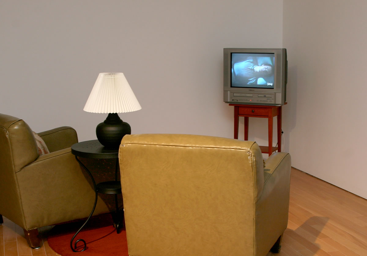 TV on stand in front of two armchairs