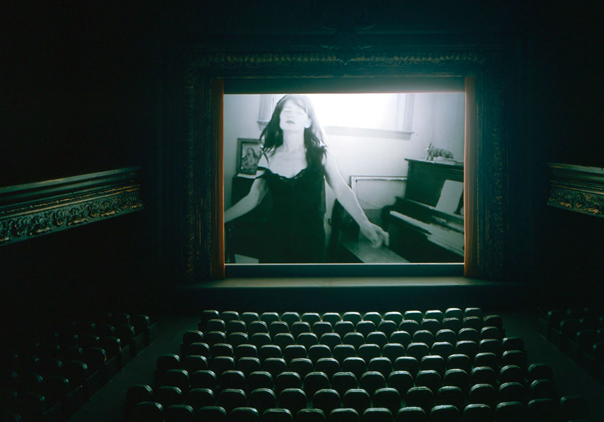 Empty theatre playing film with woman in black slip near piano