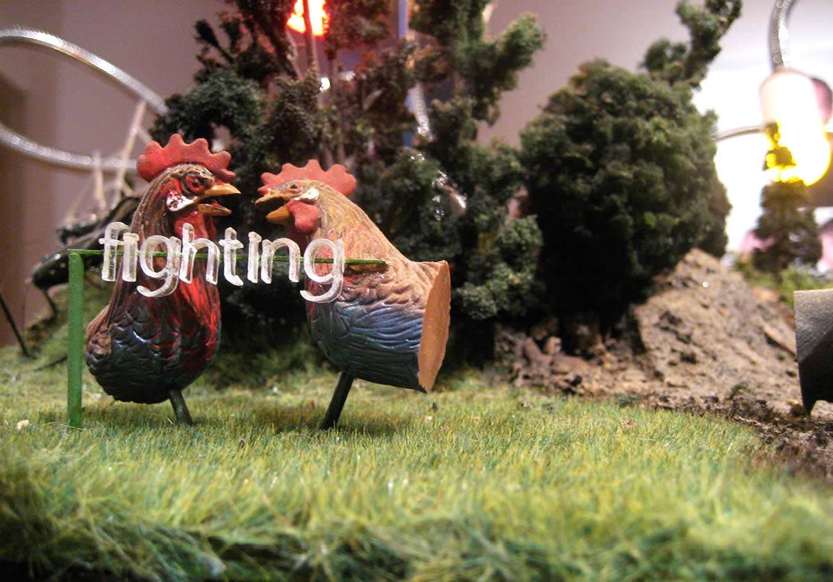 Diorama with two chickens with word