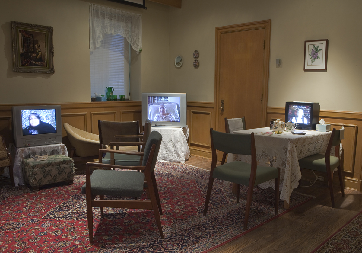 Living room with chairs and three TVs