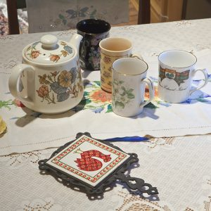 Table with teapot and mismatched mugs