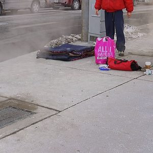 Video still of man standing on street corner with plastic shopping bag and blanket