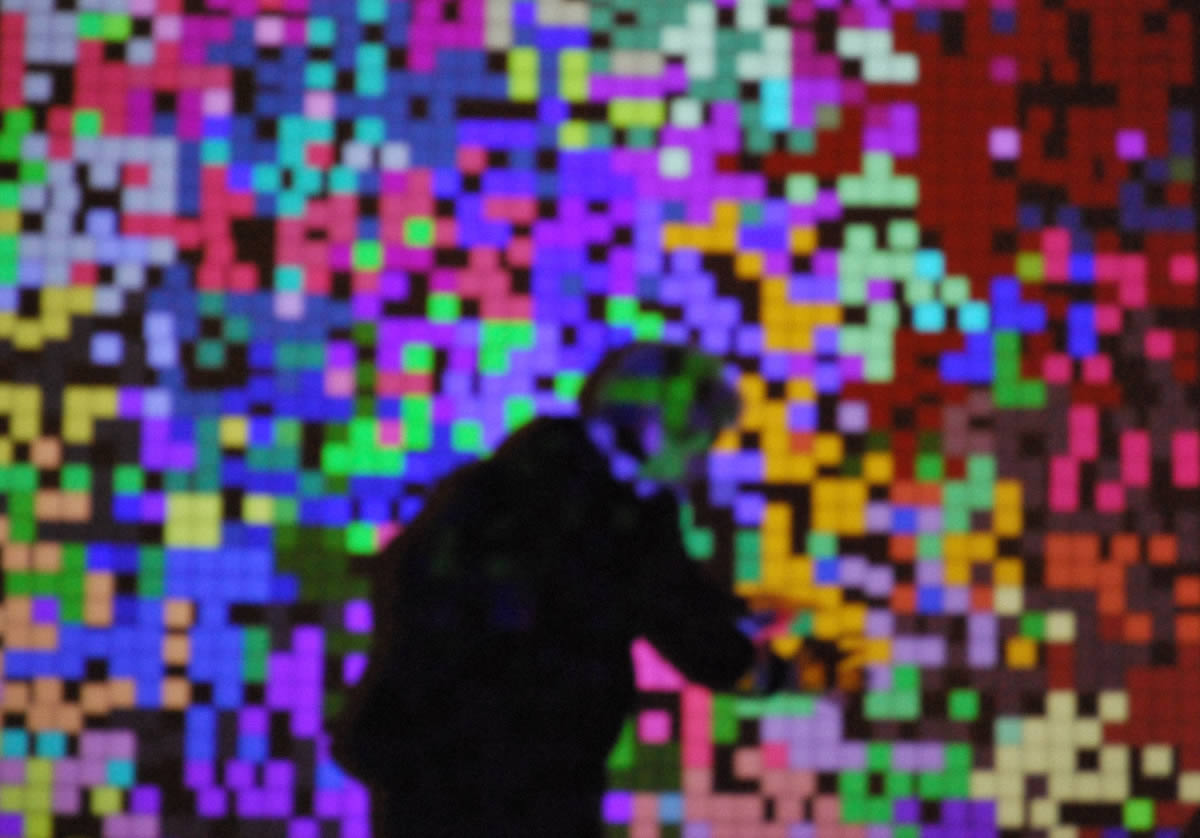 Distorted view of man in front of coloured pixels