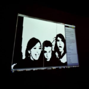 Blurry view of photo of three people on computer screen