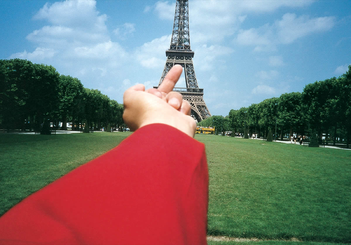 Man holding middle finger to Eiffel Tower