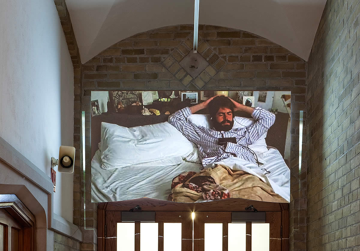 Video still of man in bed installed in Hart House