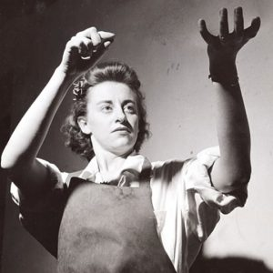 Black and white photo of woman in apron gesturing