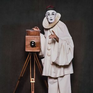 Pierrot Lunaire taking a photograph with a vintage camera