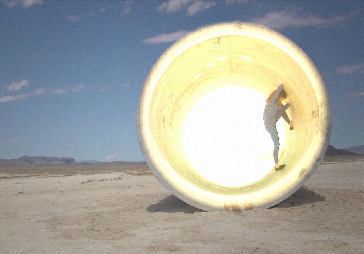 Woman standing in lit tube in desert