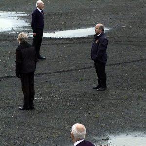 4 men in suits standing apart outdoors