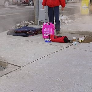 Video still of man standing on street corner with shopping bag and blanket