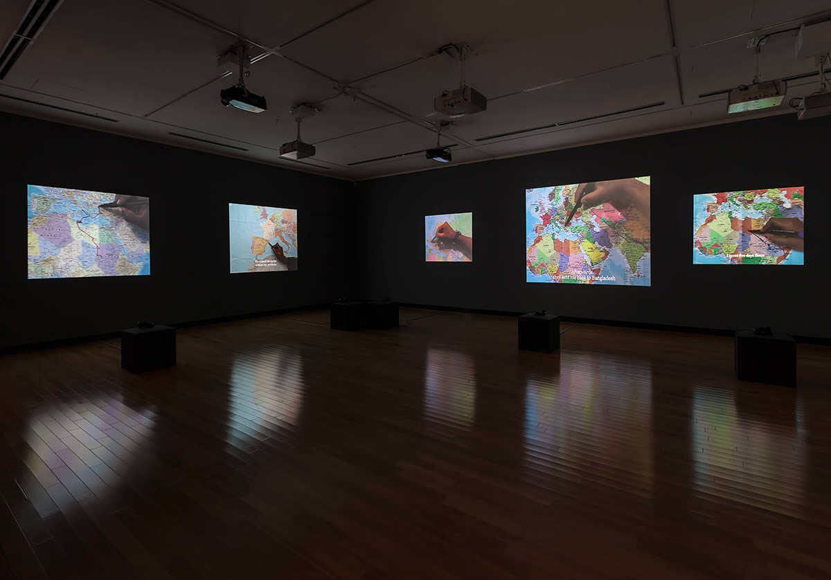 Gallery with projections of people drawing on maps