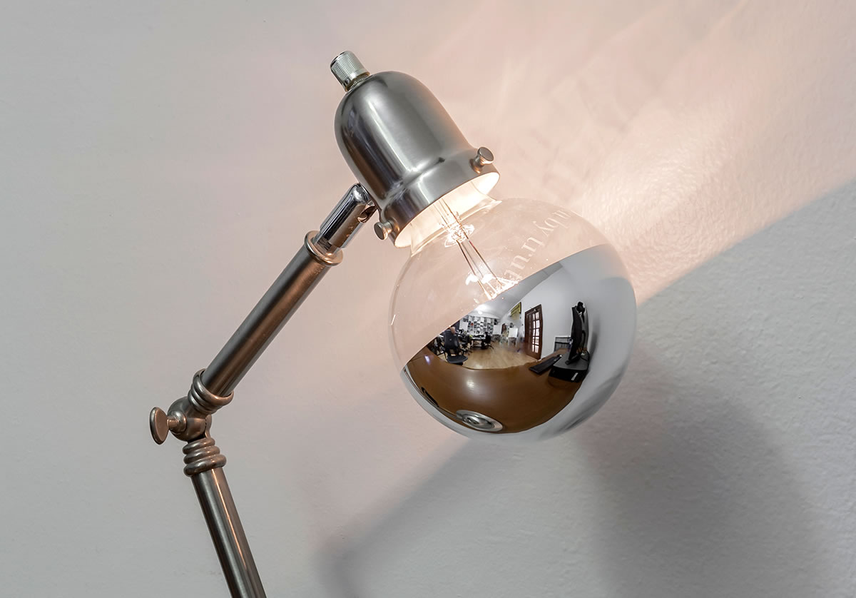 Lamp with silver-dipped bulb against wall