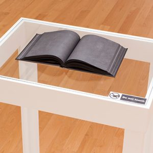 Glass table with open book with blackened pages
