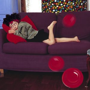 Young girl on purple couch with plates in motion