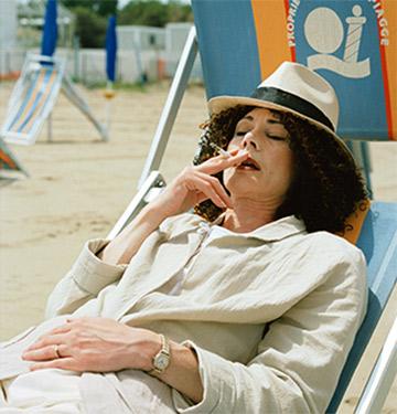 Woman sitting in beach chair smoking a cigarette