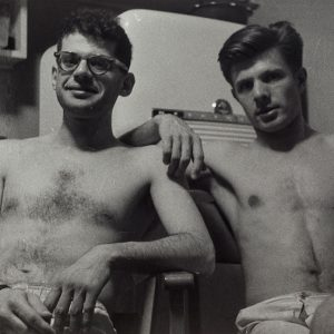 black and white film photograph of two white shirtless men. Man on the left has a pair of glasses on.