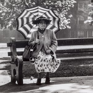 Photograph of woman in coat and skirt holding striped umbrella