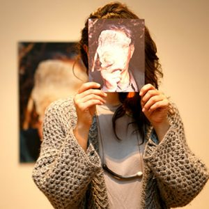 Woman holding a picture of a rock in front of her face