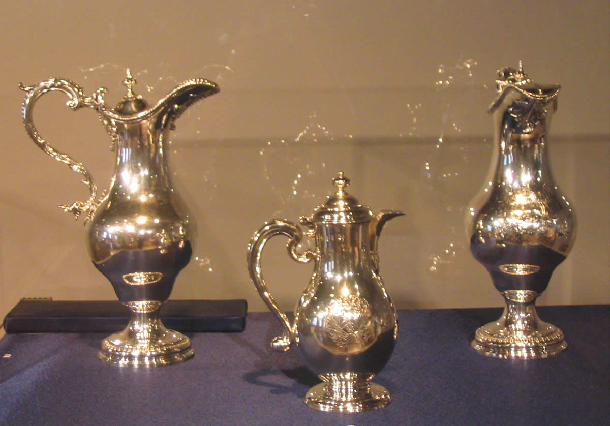 Three silver pitchers on display