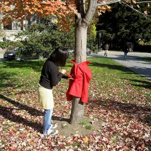 Woman putting red coat on tree