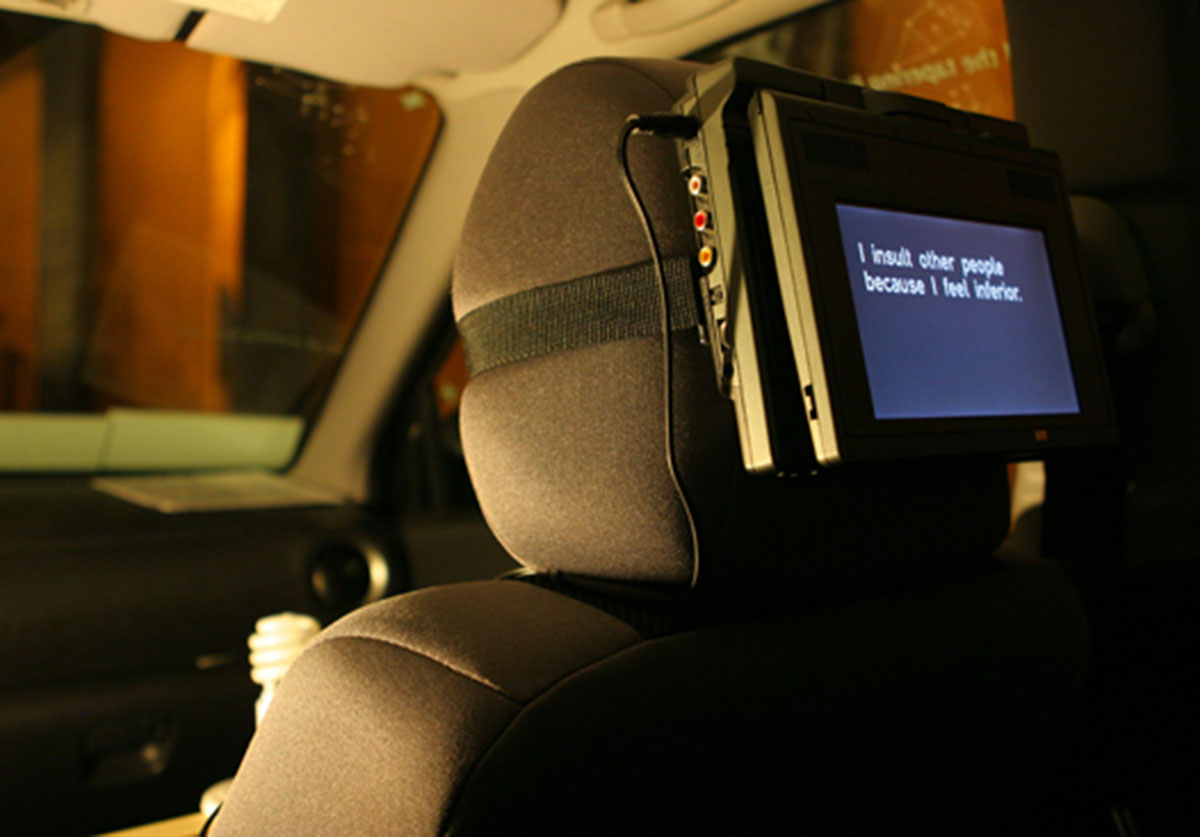 Car seat with screen strapped to headrest