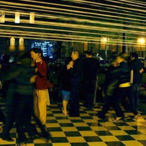 Couples dancing in motion on checkered dancefloor