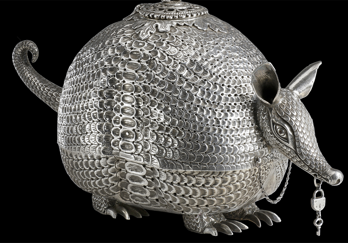 Silver armadillo holding lock and key with little man on top