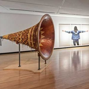 Wood horn shaped sculpture next to framed photograph of a woman's wingspan