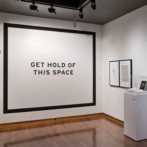 """A white surface with the text """"Get Hold of This Space"""""""