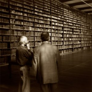Two men in library with wall of books