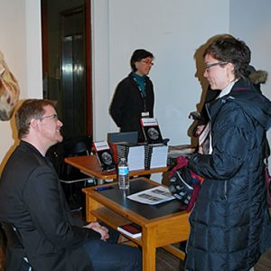 Matthew Brower talking with woman at book launch