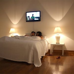 Two people in bed under TV screen
