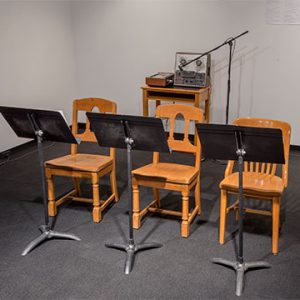 Three chairs in front of three music stand with microphone up to speaker in back