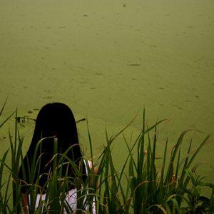 Woman sitting near green water