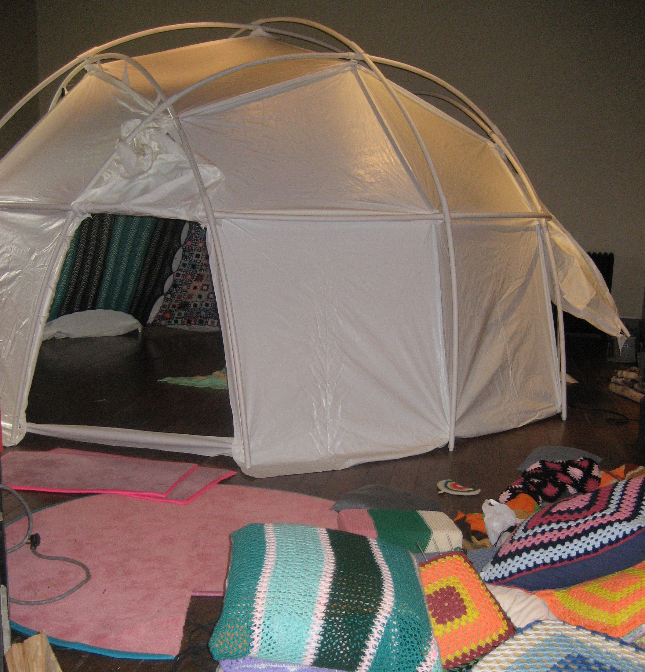 A yurt installed in the gallery with crochet pillows surrounding it