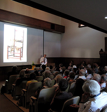 Audience watching lecture with chair on screen