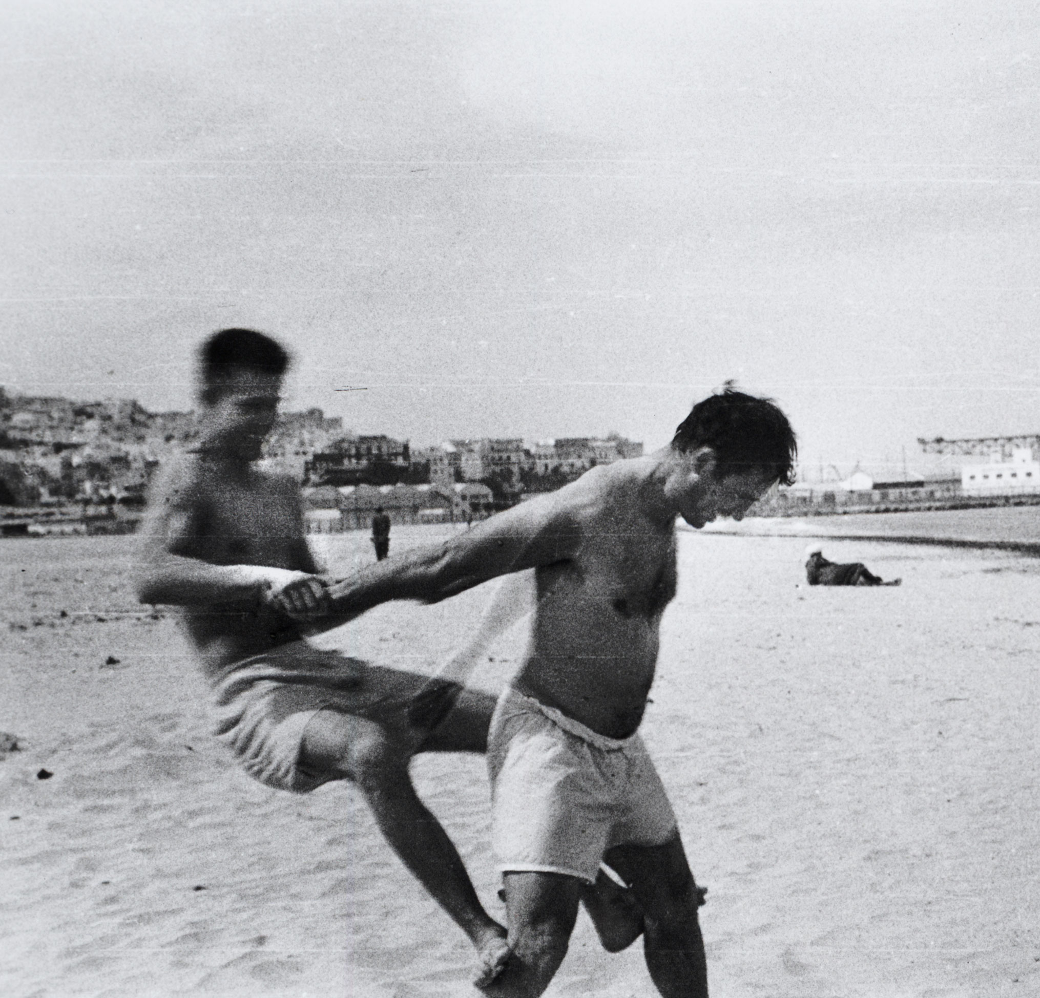 Two men in bathing suits embracing