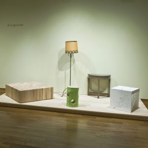Wooden table, lamp, tree stump, and two side tables on display