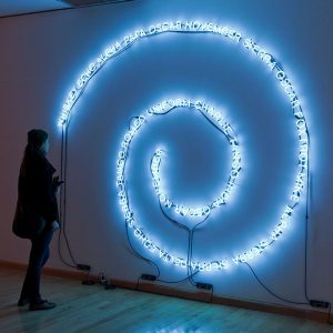 """Installation view of Will Kwan: Multi-lateral, 2009. Will Kwan, X-ray, Yankee, Zulu, 2009. 3 wall-mounted neons, hanging hardware, cables, transformers. Approximately 12 feet diameter each. Image credit: Toni Hafkenscheid"""