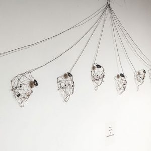 Several wire structures connected through string hung on wall