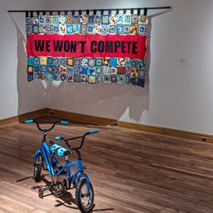 """Crochet tapestry that reads """"We Won't Compete"""" in front of two tricycles"""