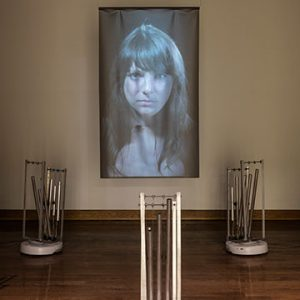 Projected image of woman in front of 3 sets of chimes