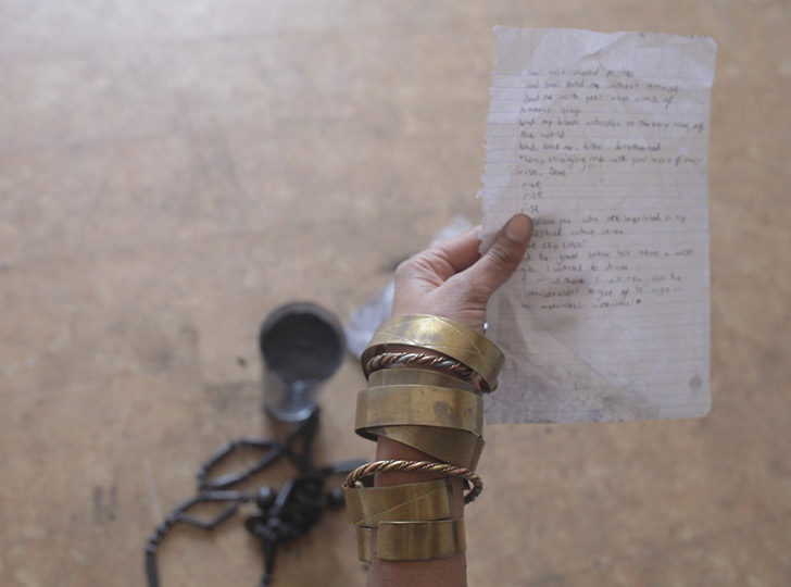 Arm with gold bracelets holding notebook paper