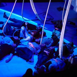 People laying on floor and touching under blue light