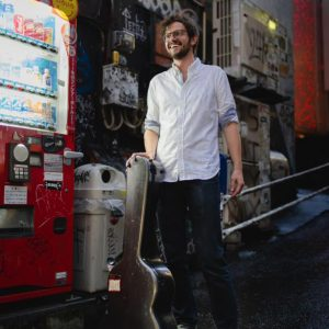 Graham Banfield holding guitar case in front of vending machine on street